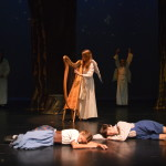 Hansel (Henry Hubbard) and Gretel (Lynn Loftus) are protected by angels (Katie Nelson) in the Black Forest.